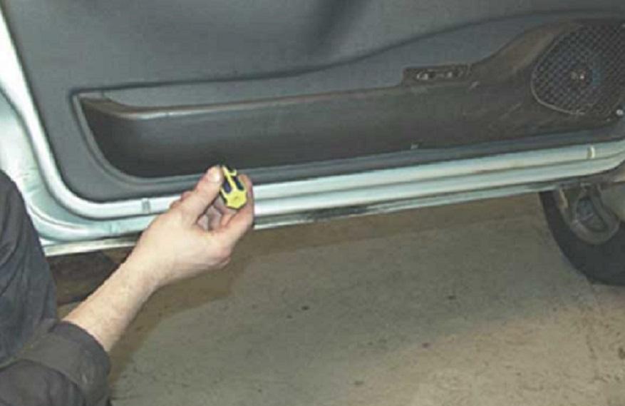 Откручиваем саморезы в нижней части накладки двери